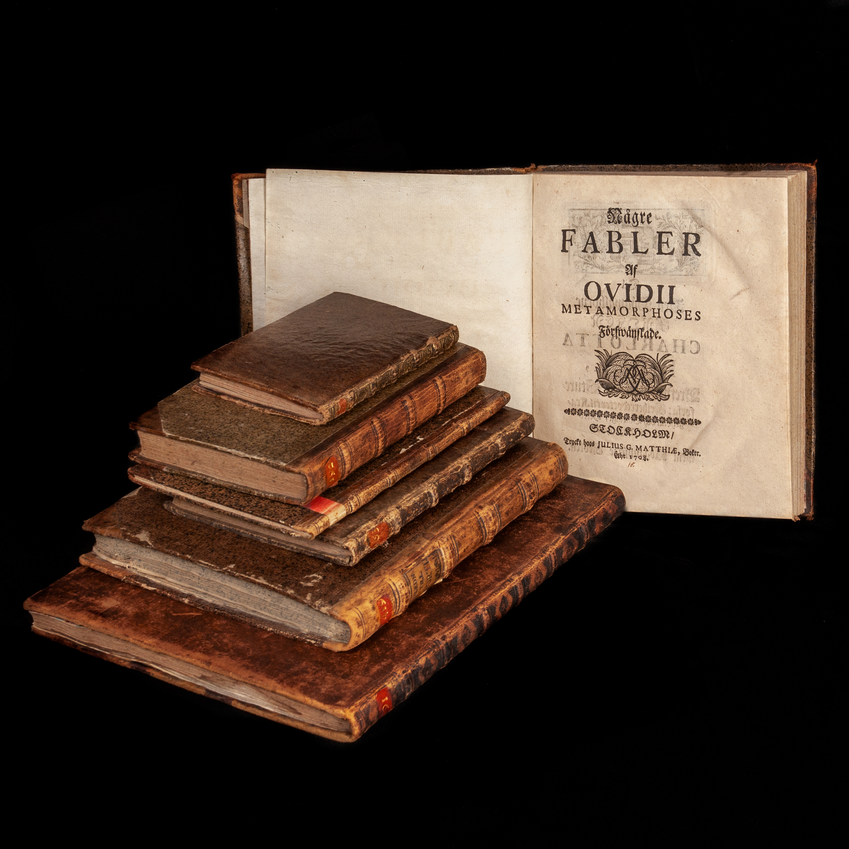 a pile of brown leather halfbindings with sprinkled paper on the covers