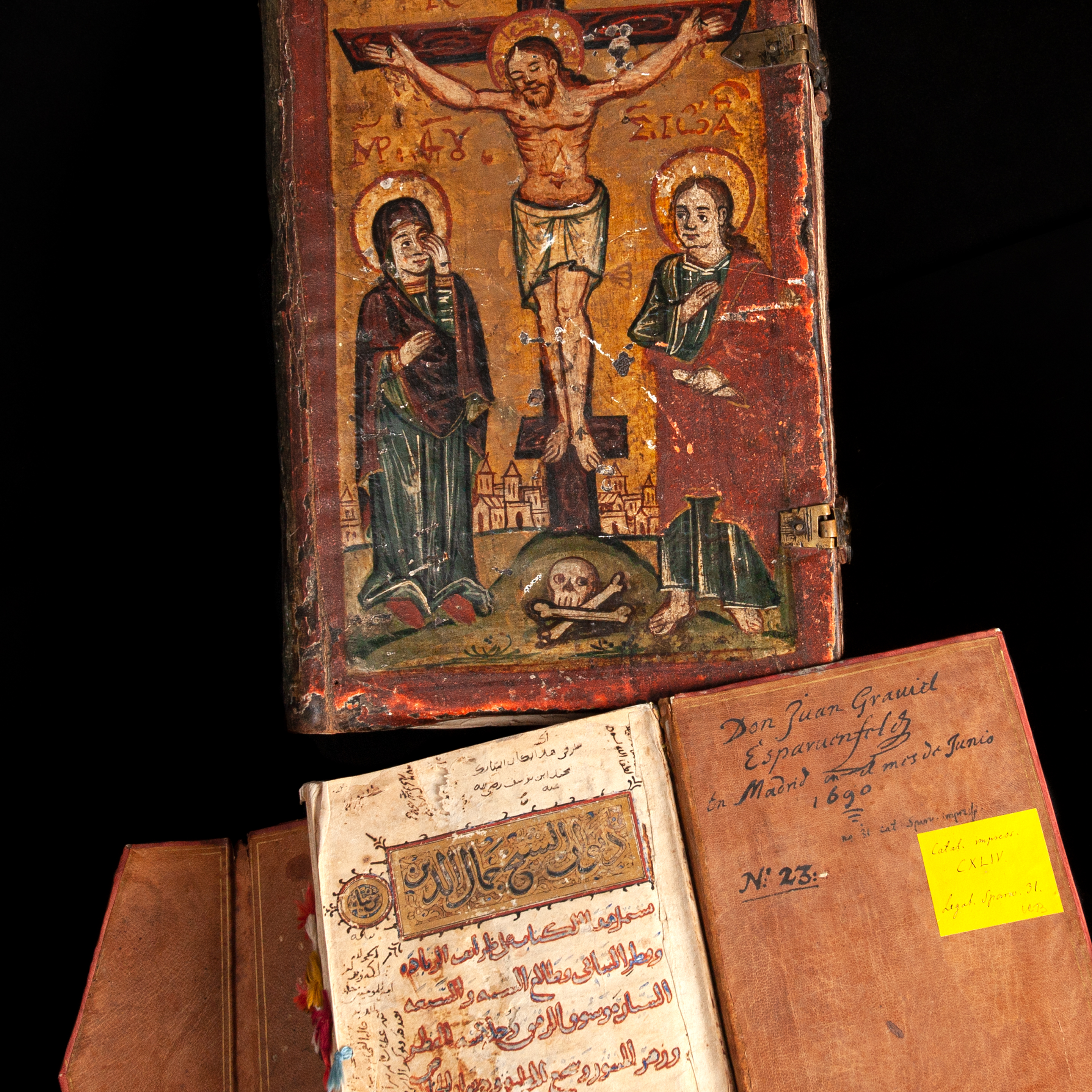 two books, one with arabic text and the other with a crucifixion scene painted on the cover